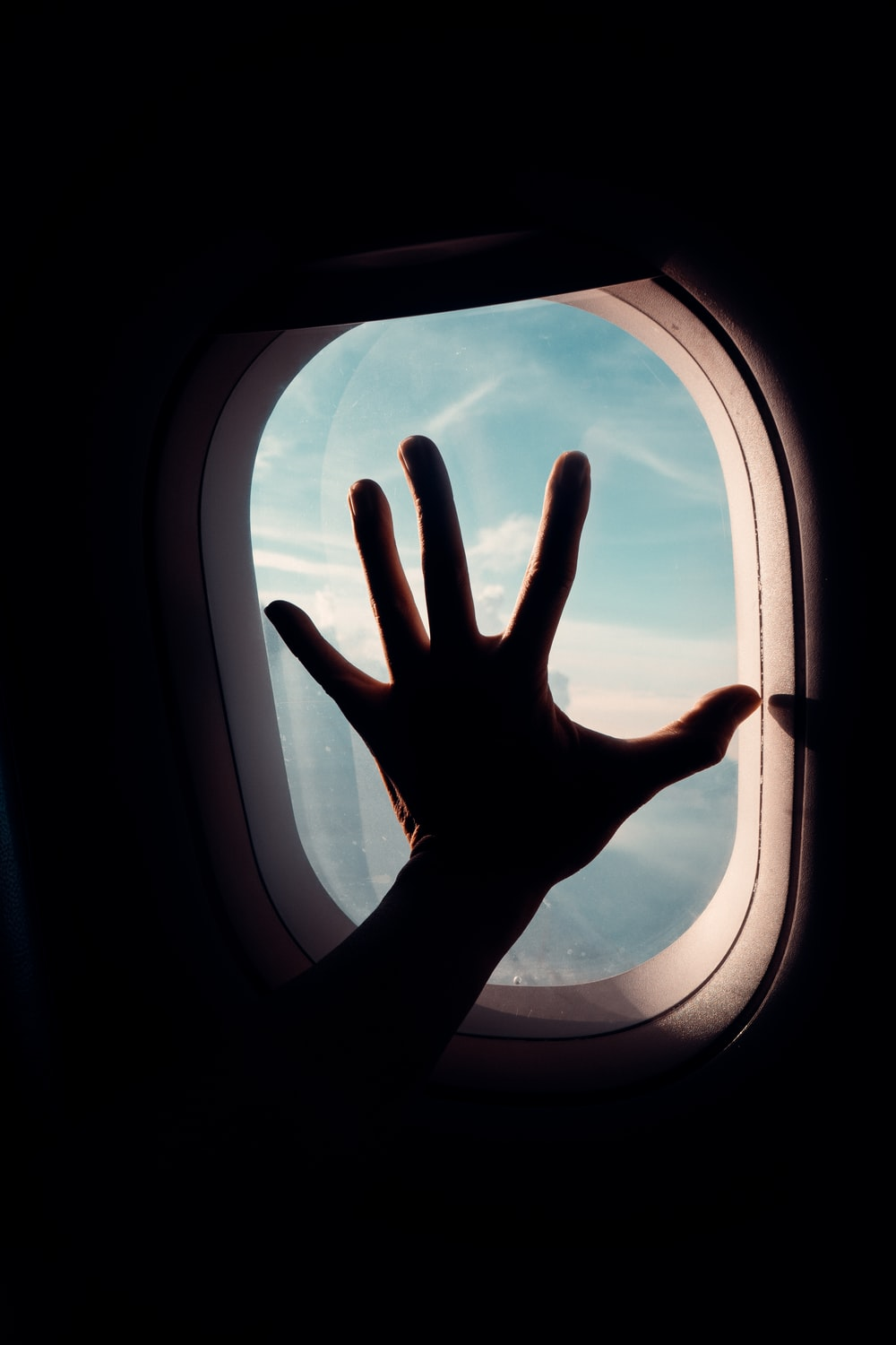 persons hand on airplane window