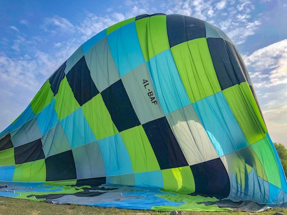 blue green and yellow hot air balloon on beach