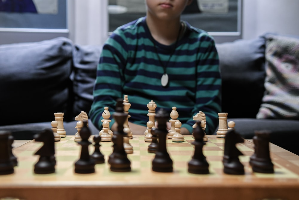 boy in green and black striped sweater playing chess