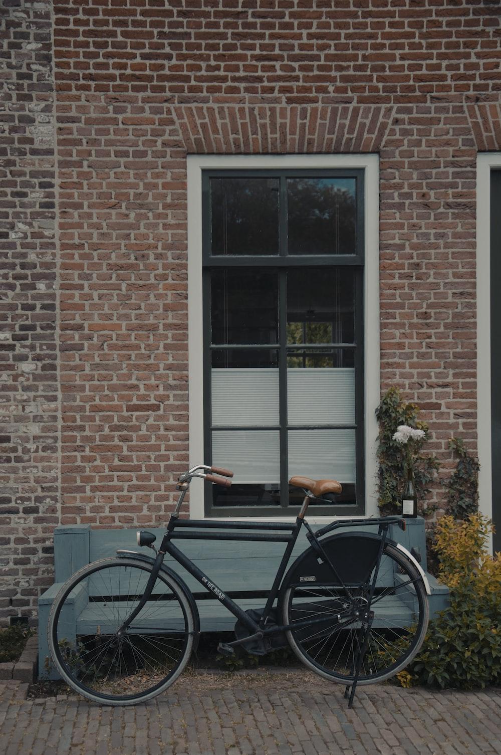 black bicycle beside brown brick wall