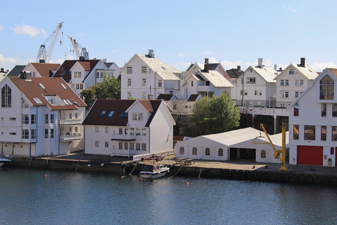 Houses on the Island Risoy, part of the town Haugesund, located on the west coast of Norway, between Bergen and Stavanger. Scandinavia, Europe. Cranes of a shipyard in the background.