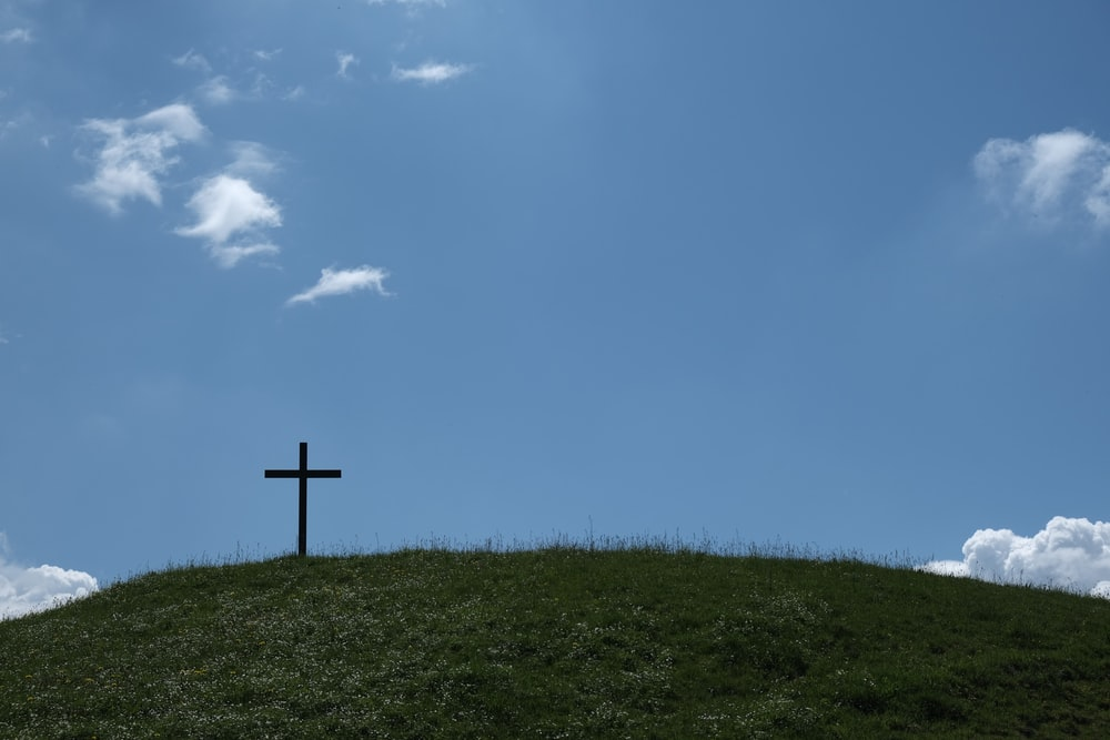 black cross on green grass under blue sky during daytime