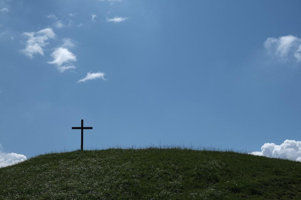 black cross on green grass under blue sky during daytime