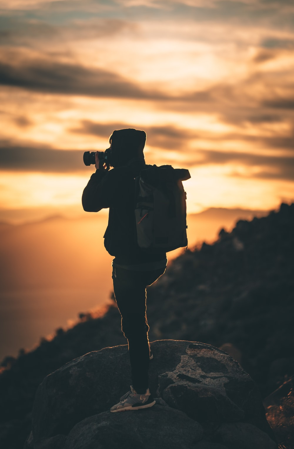 silhouette of man holding camera during sunset