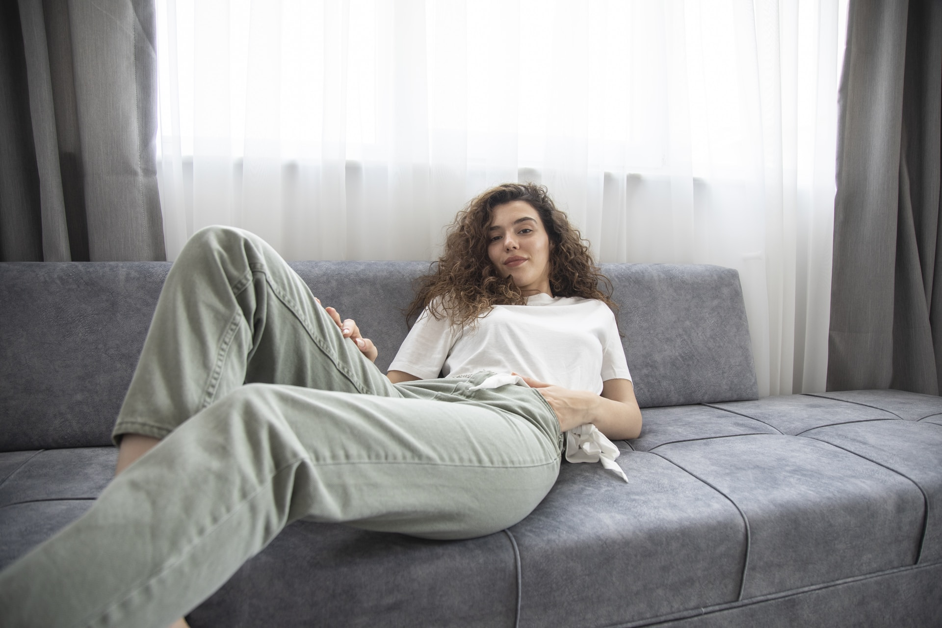 woman in green shirt lying on gray couch