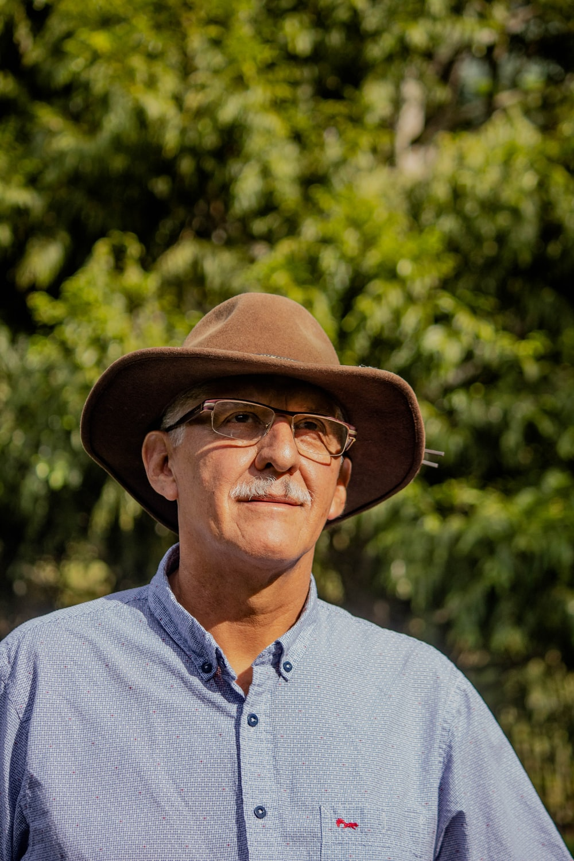 man in gray button up shirt wearing brown fedora hat
