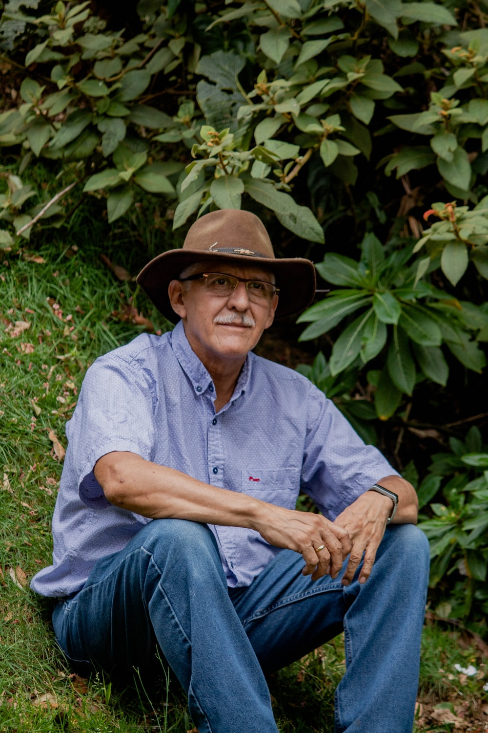 man in blue dress shirt and blue denim jeans wearing brown cowboy hat sitting on green