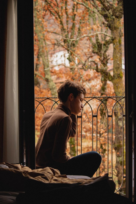 woman in brown long sleeve shirt sitting on window