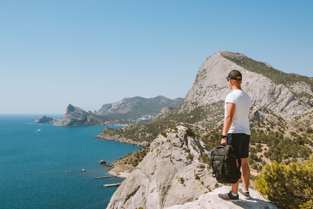 man in white t-shirt standing on rocky mountain looking at the sea during daytime