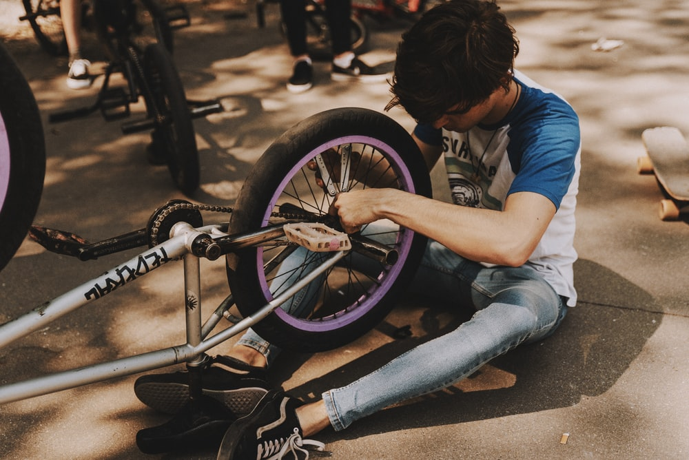man in blue t-shirt and blue denim jeans sitting on gray concrete pavement