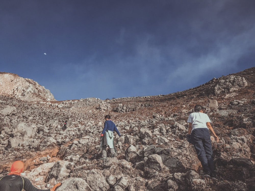man in white jacket and blue denim jeans walking on rocky hill under blue sky during