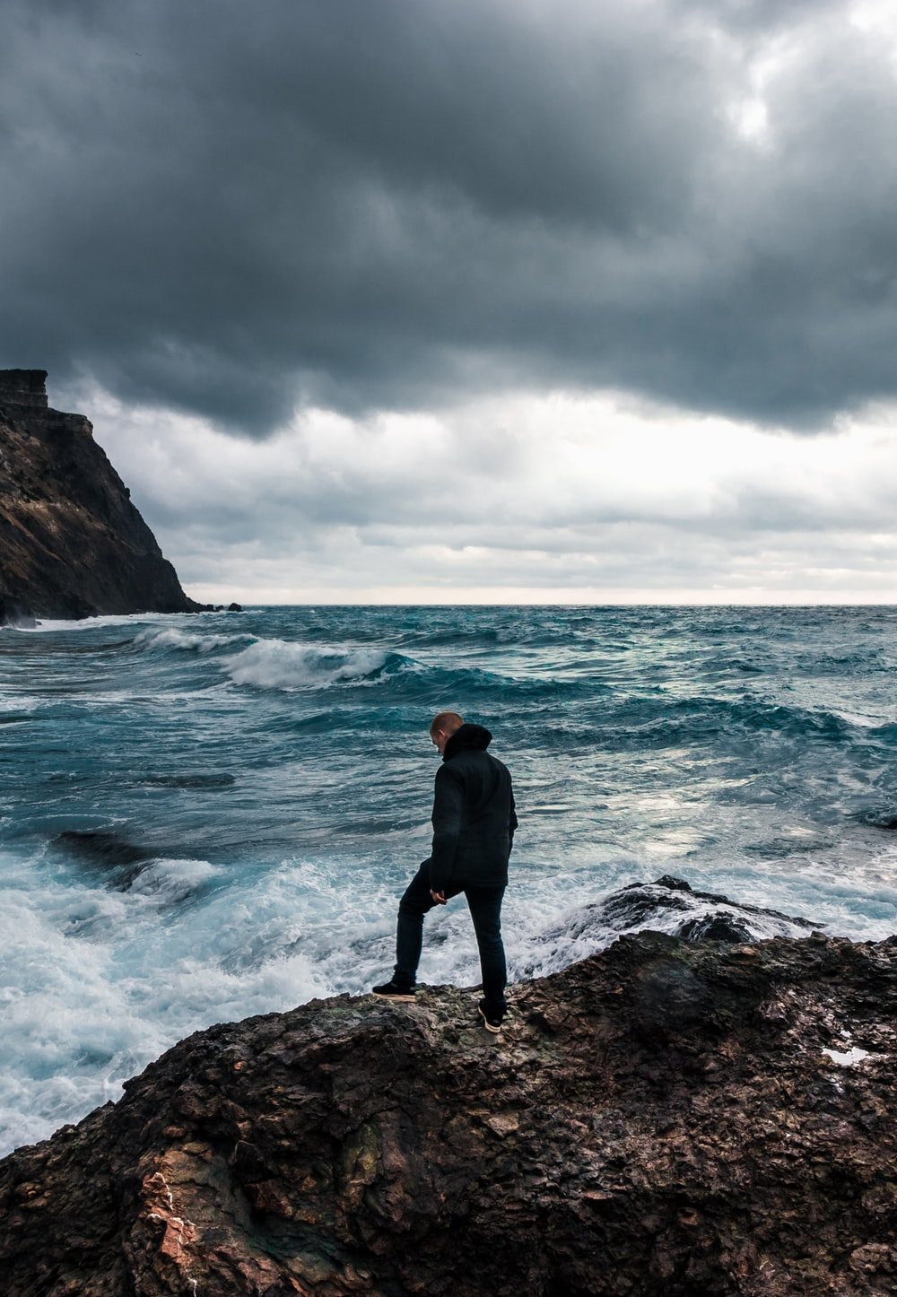 man in black hoodie standing on rock formation near sea under cloudy sky during daytime