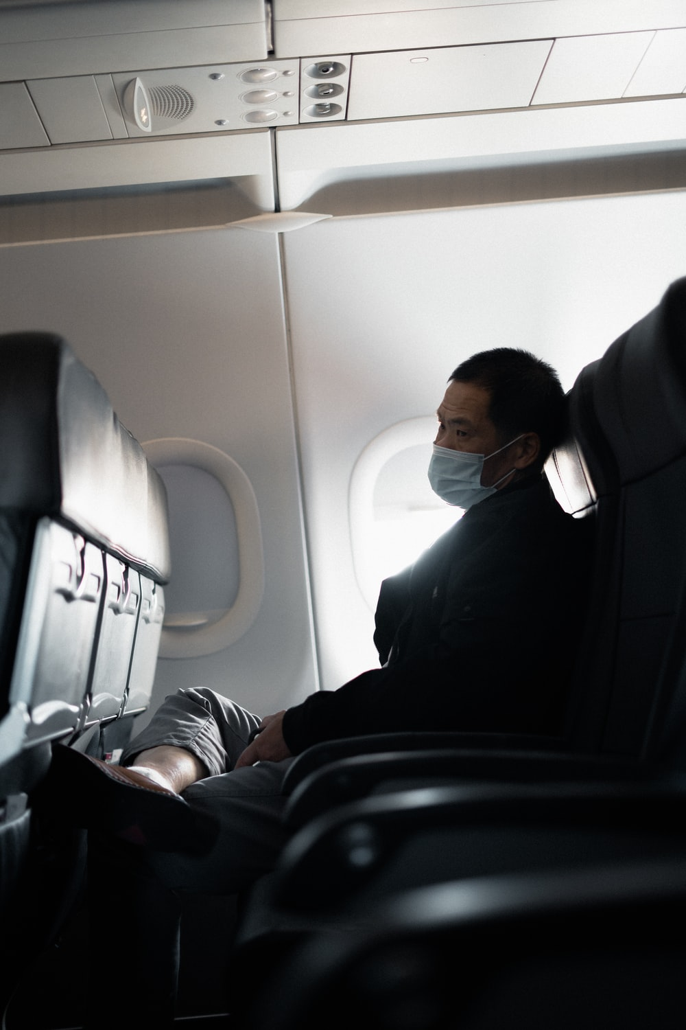 man in black suit sitting on airplane seat