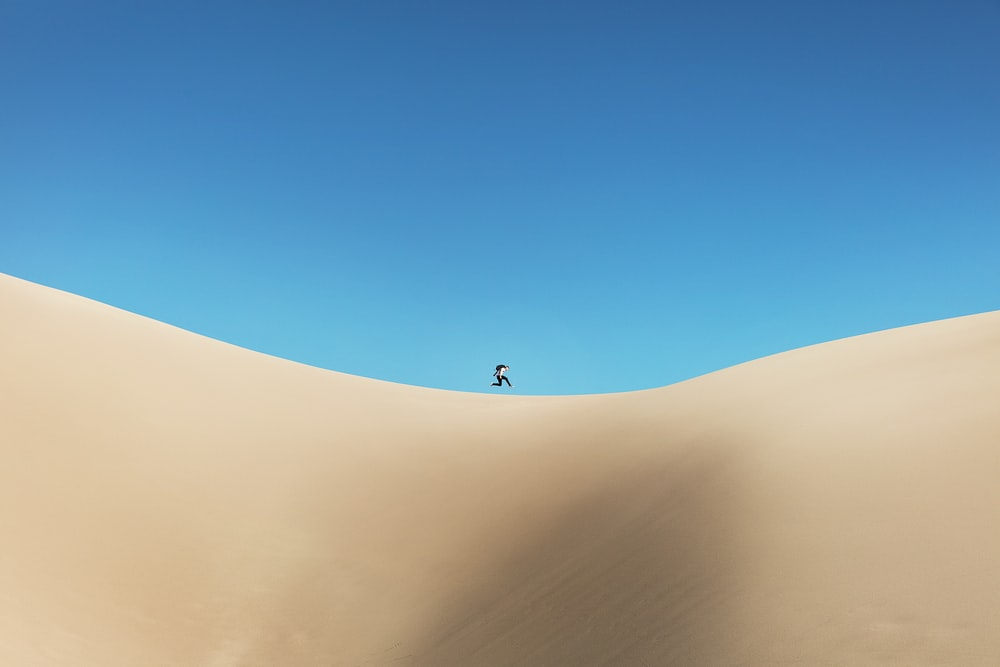 person walking on desert under blue sky during daytime