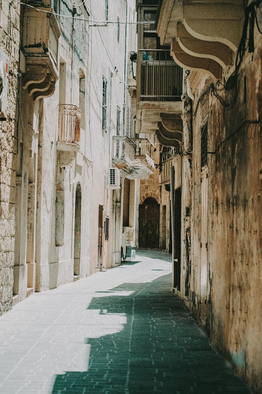 empty hallway between concrete buildings during daytime