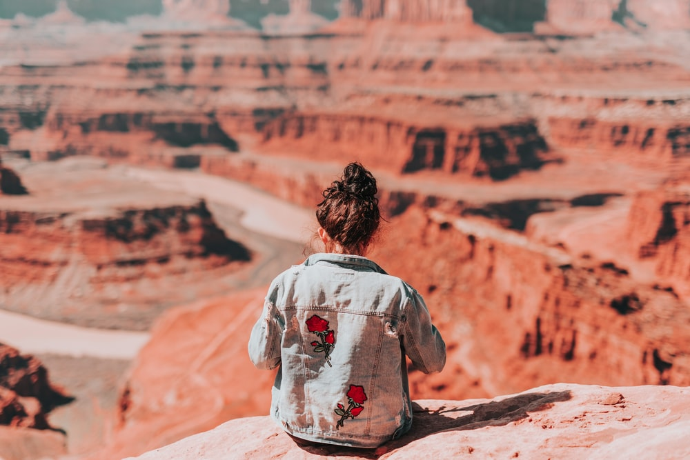 woman in white and red floral shirt sitting on rock formation during daytime