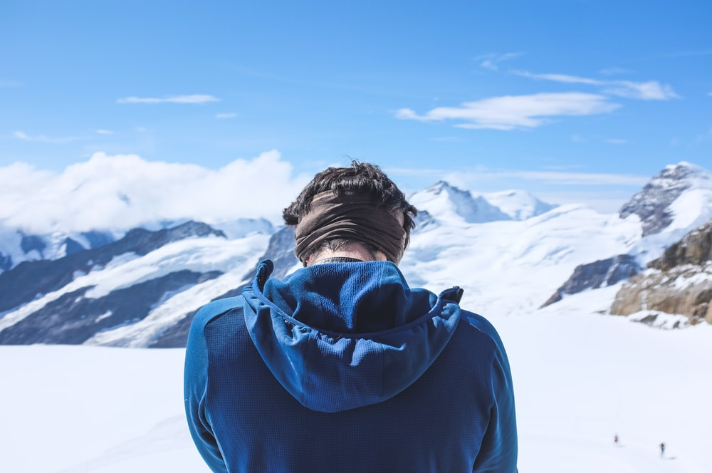 man in blue hoodie standing on snow covered ground during daytime