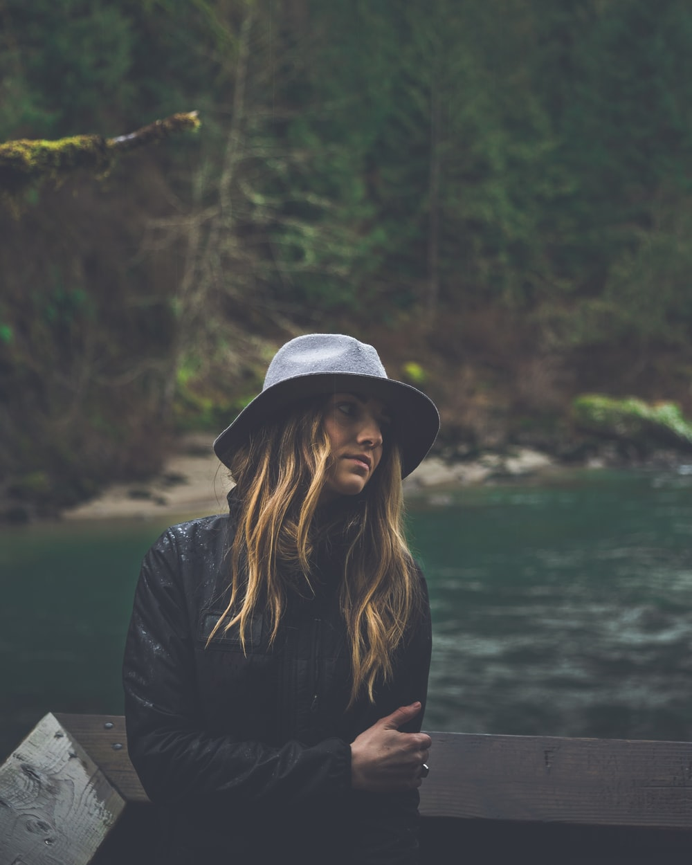 woman in black jacket and white hat sitting on wooden dock during daytime