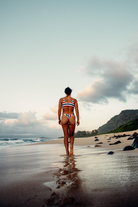 woman in white bikini standing on beach during daytime