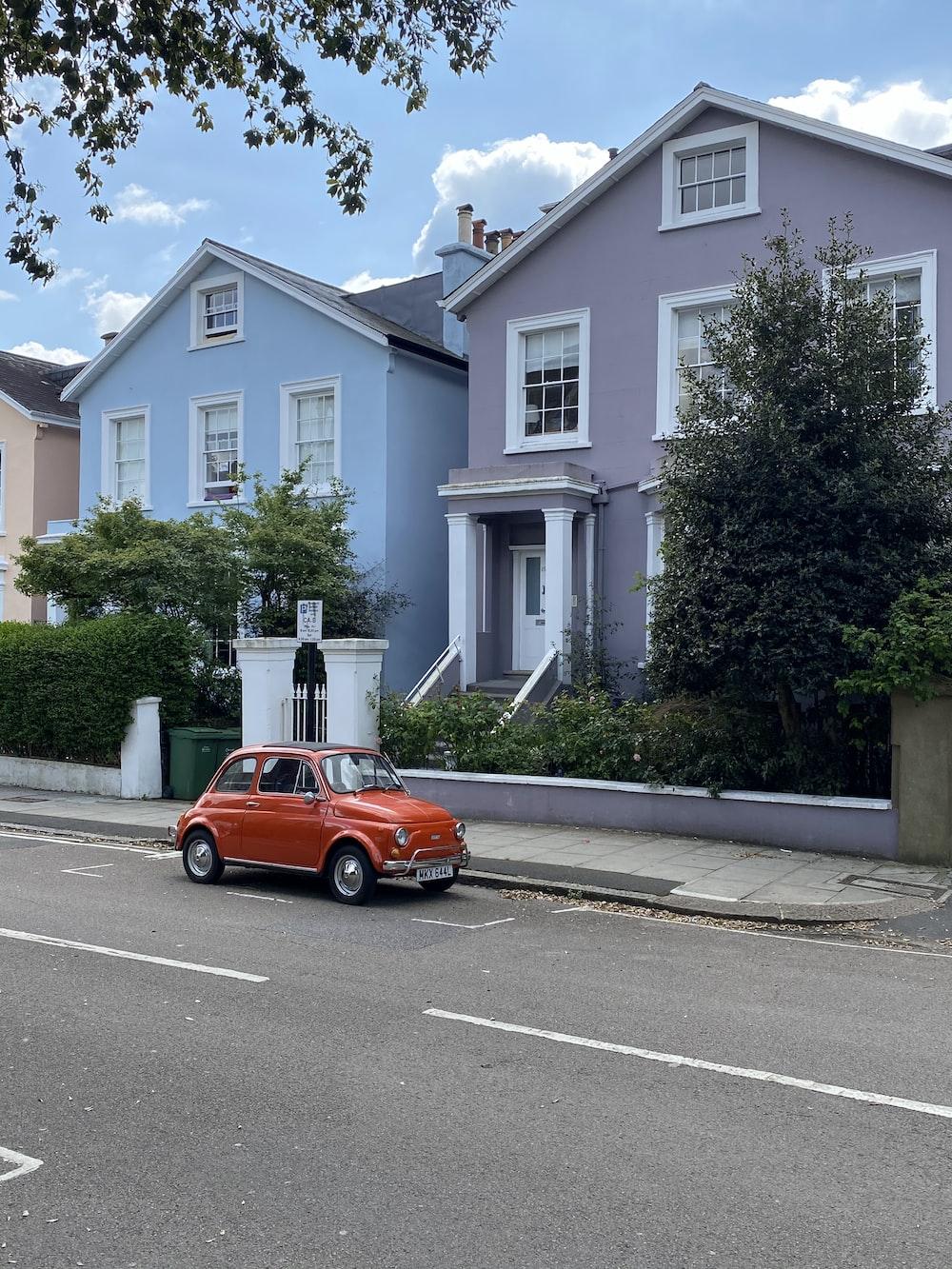 orange car parked near green tree during daytime