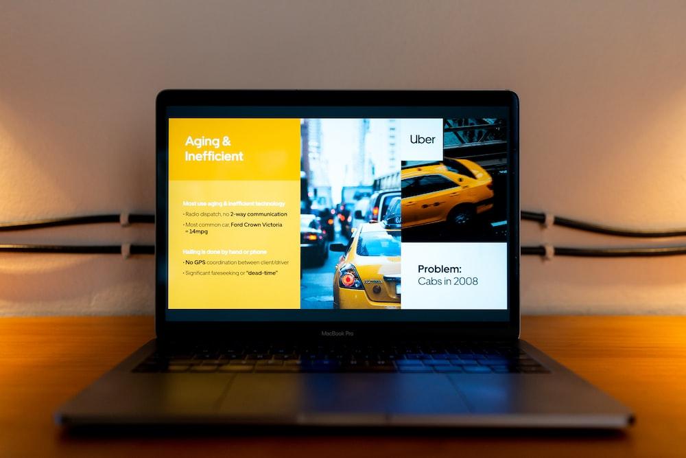 black laptop computer turned on displaying man in yellow shirt