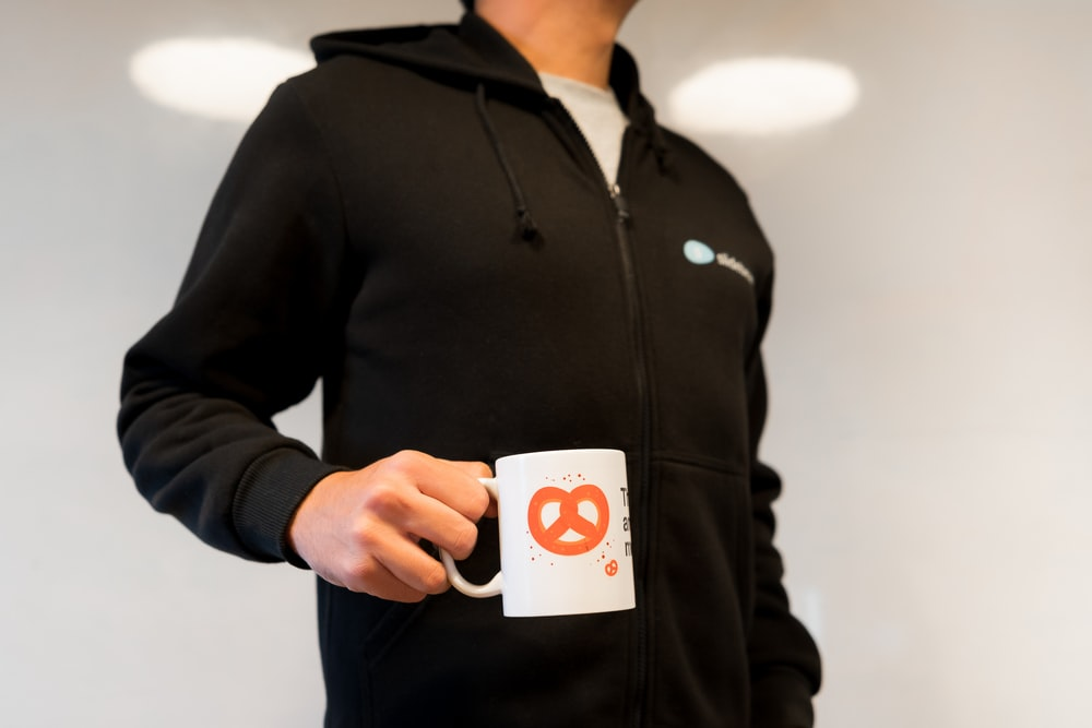 man in black zip up jacket holding white and orange card