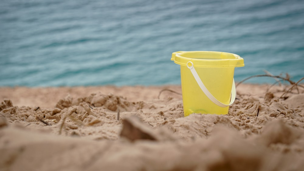 yellow plastic bucket on brown sand near body of water during daytime