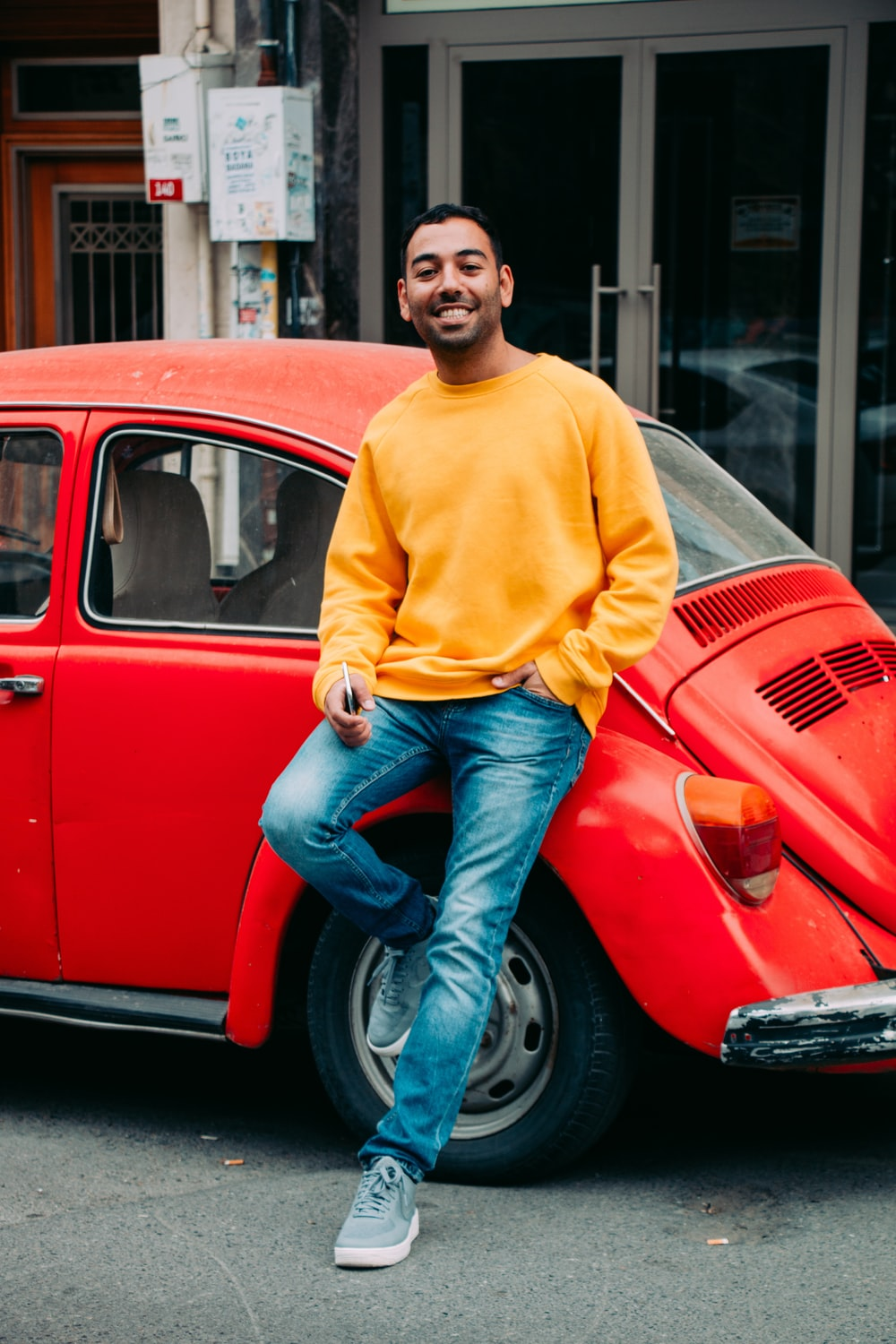 man in yellow sweater and blue denim jeans sitting on red volkswagen beetle