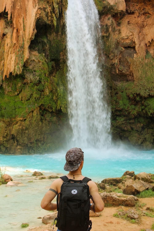 woman in black bikini sitting on brown rock near waterfalls during daytime
