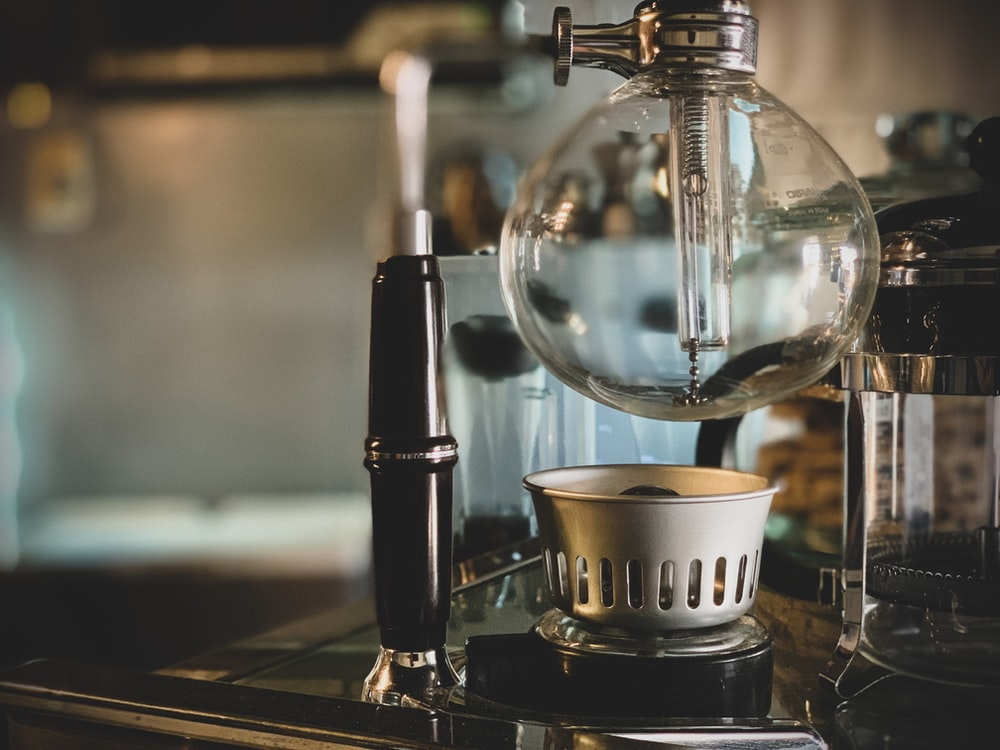 black and silver coffee maker beside white ceramic cup