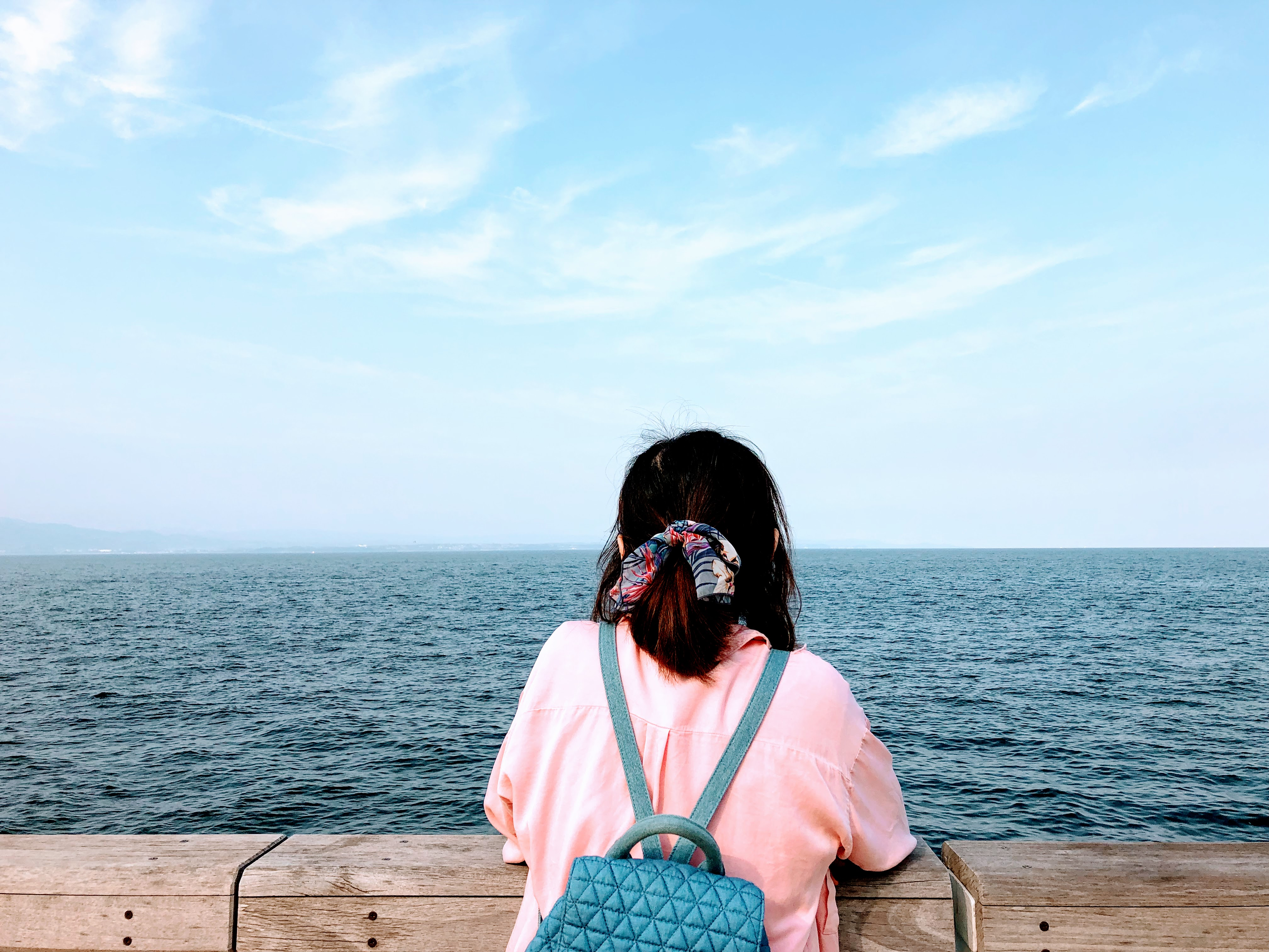 woman in pink shirt sitting on brown wooden bench looking at the sea during daytime