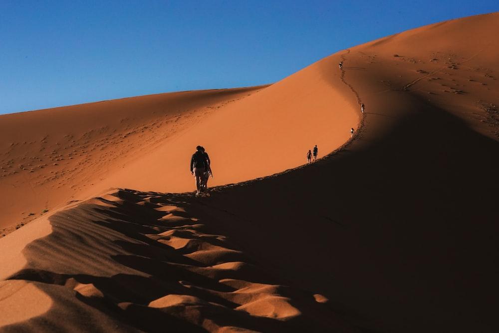 person walking on sand dunes during daytime