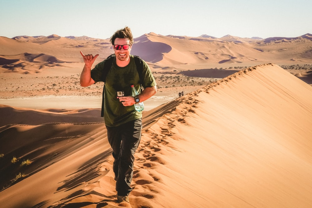 man in black crew neck t-shirt and black pants standing on brown sand during daytime