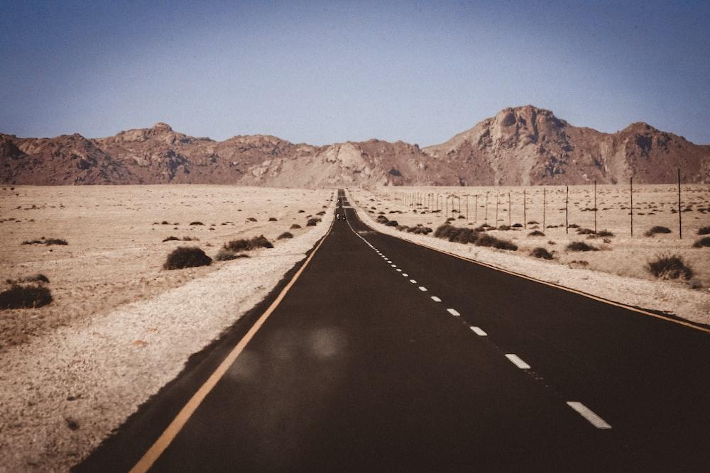 black asphalt road in between brown field under blue sky during daytime