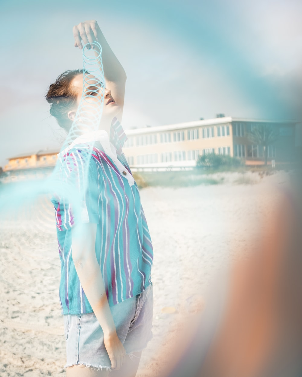 woman in blue and white stripe shirt standing on beach shore during daytime