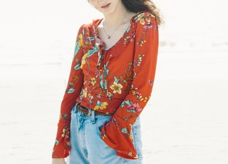 woman in red and blue floral long sleeve shirt standing on white sand during daytime