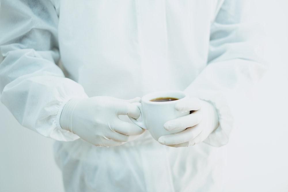 person in white dress shirt holding white ceramic mug
