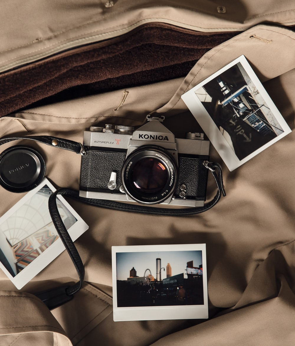 black and silver dslr camera on brown textile