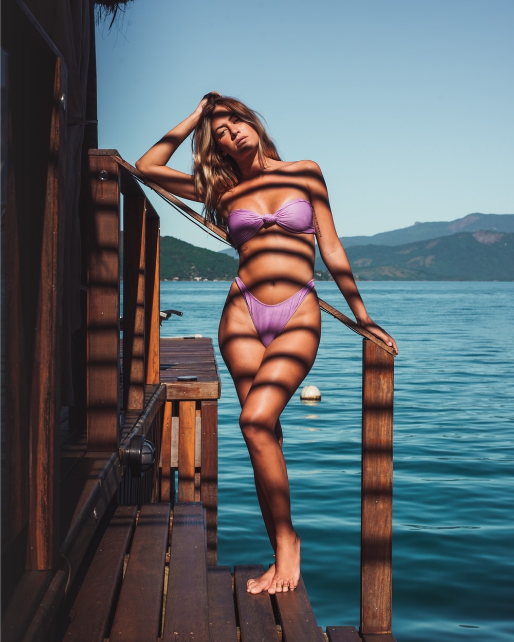 woman in pink bikini standing on wooden dock during daytime