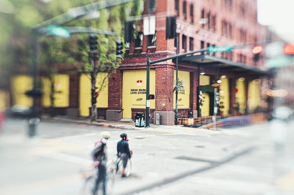 people walking on sidewalk near brown building during daytime