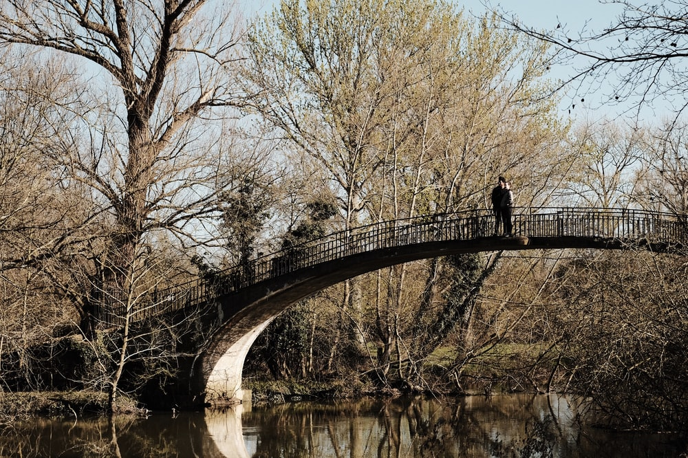 man in black jacket and pants standing on bridge over river during daytime