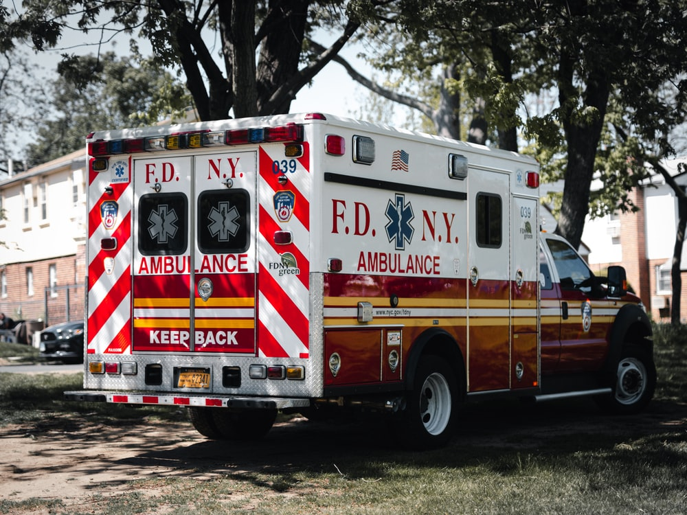 red and white ambulance truck parked near green trees during daytime