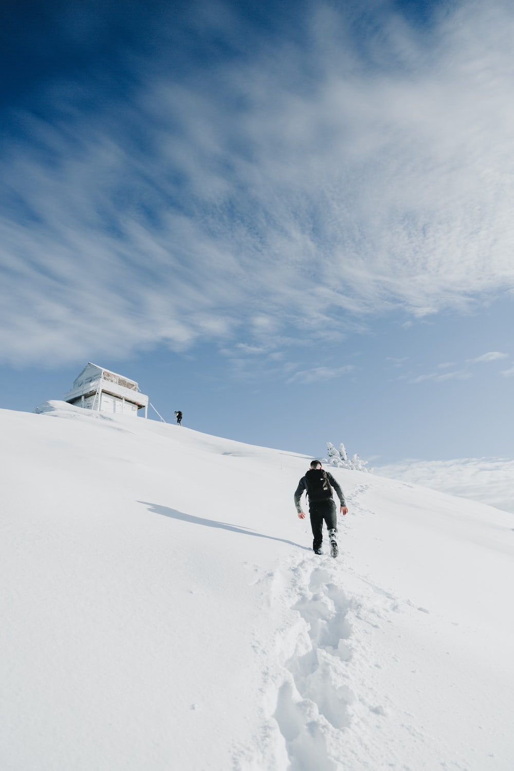 person in black jacket walking on snow covered ground under blue sky during daytime
