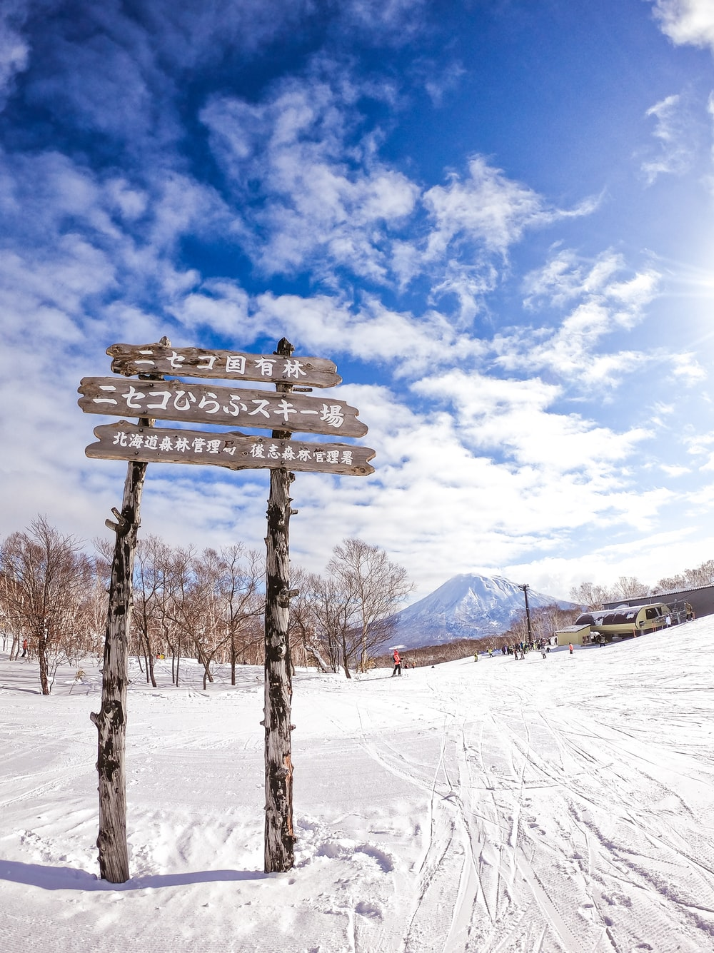 brown wooden bench on snow covered ground under blue and white cloudy sky during daytime