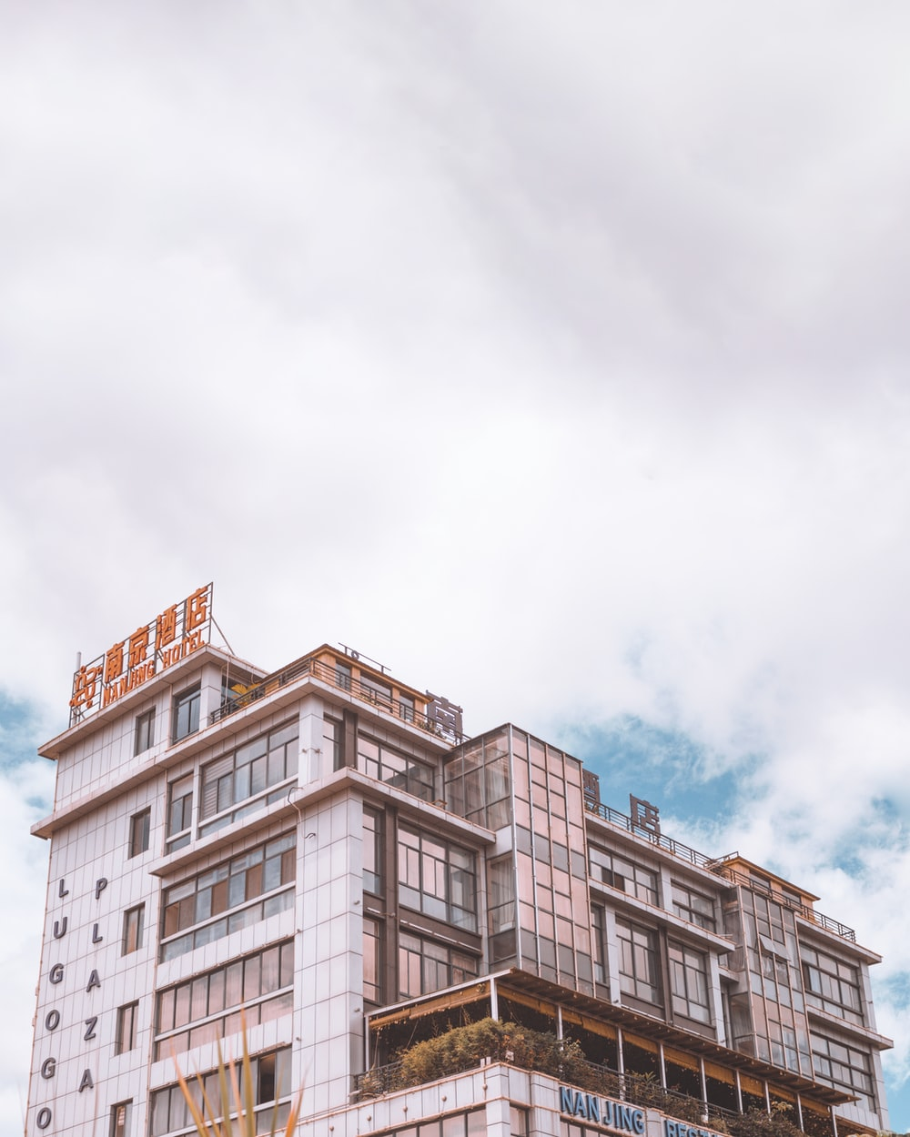 white and brown concrete building under white clouds during daytime