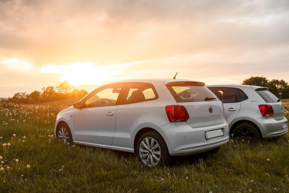 white sedan on green grass field during sunset