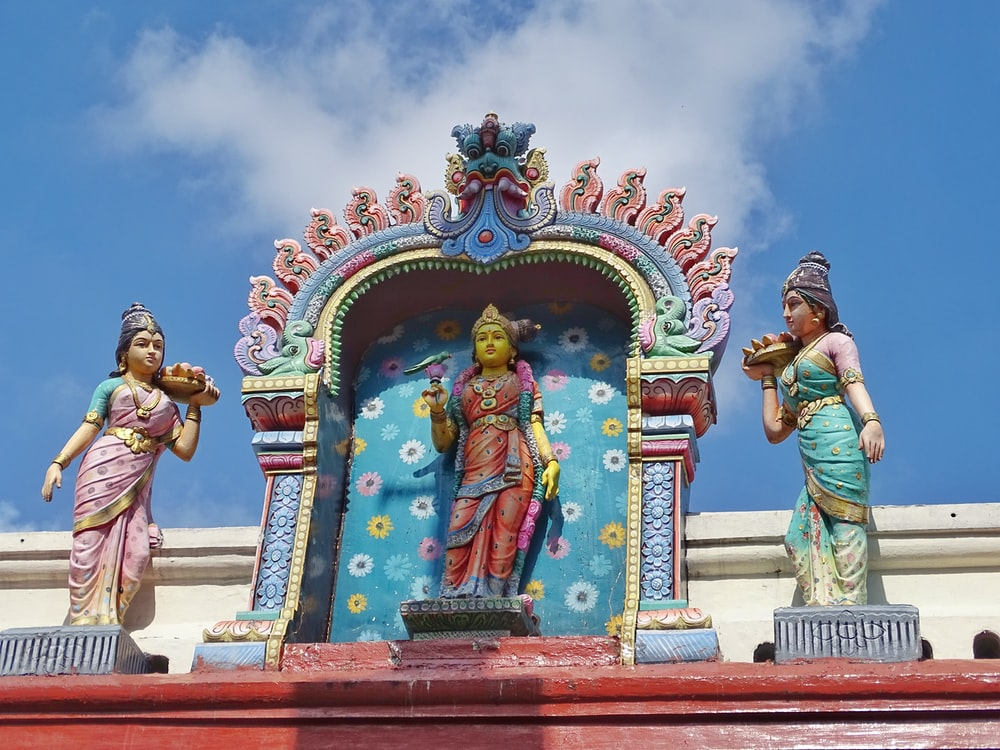 man in green shirt and blue denim jeans standing in front of hindu deity statue