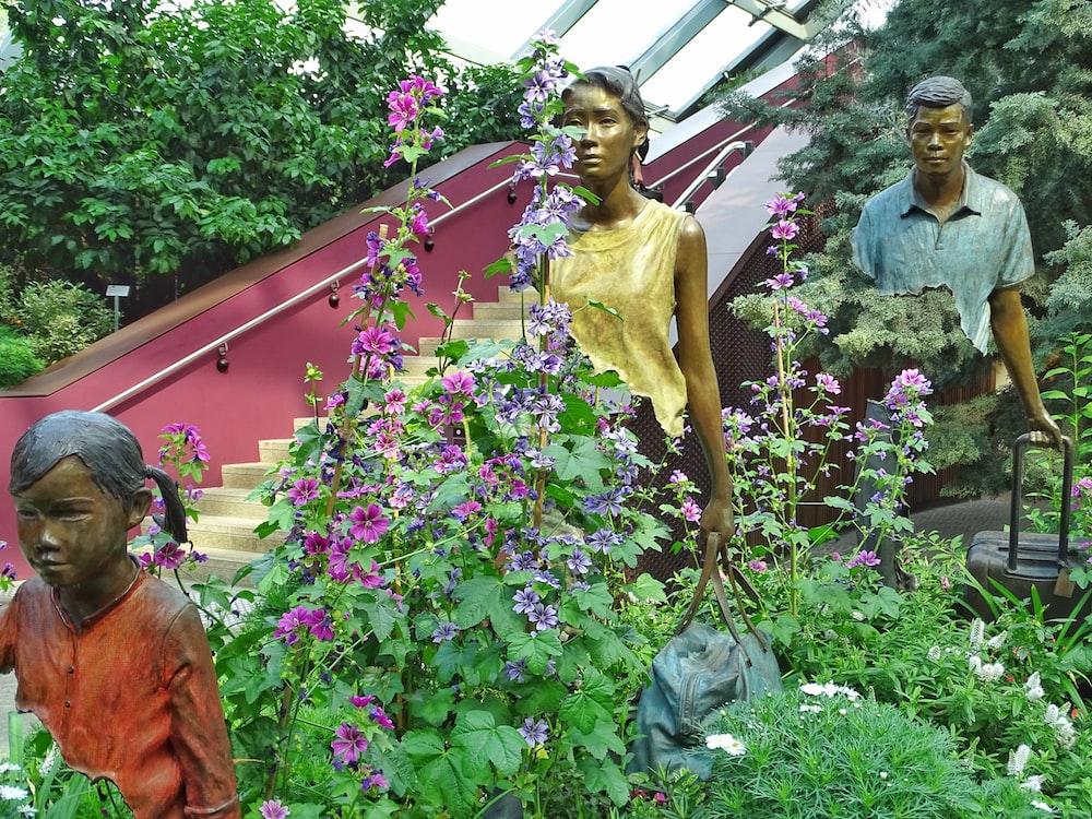 woman in yellow dress standing beside purple flower
