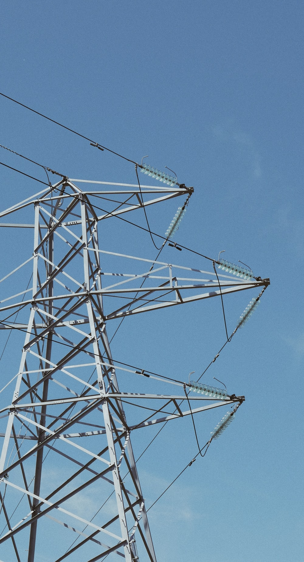 white metal electric towers under blue sky during daytime