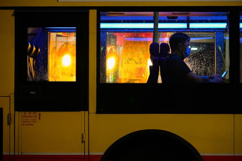 man in black jacket sitting inside yellow bus during daytime